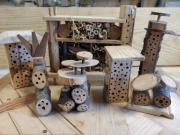Différents hôtels à insectes réalisés dans des buches et des cubes de palettes.